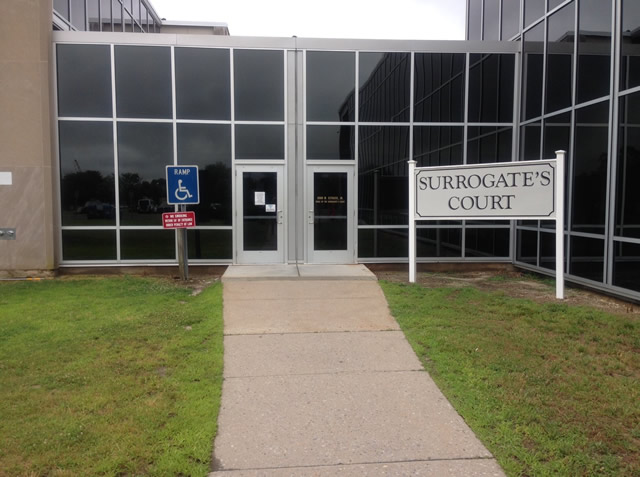 Two single door entrances to the courthouse. There is a walkway leading to the two doors with a lawn area on both sides of the walkway. There is ADA signage on the lawn on the left and a 'Surrogate's Court' sign on the right lawn.