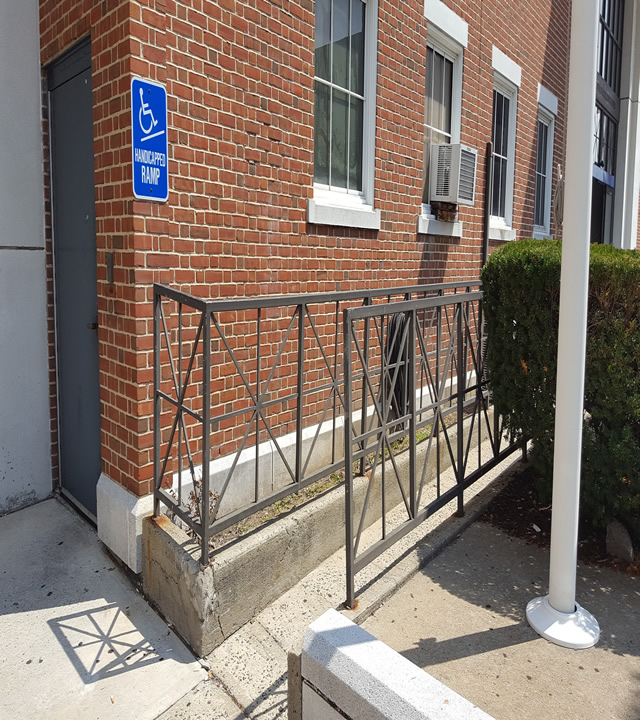 An ADA-accessible ramp, there is ADA signage against the building on the left side.