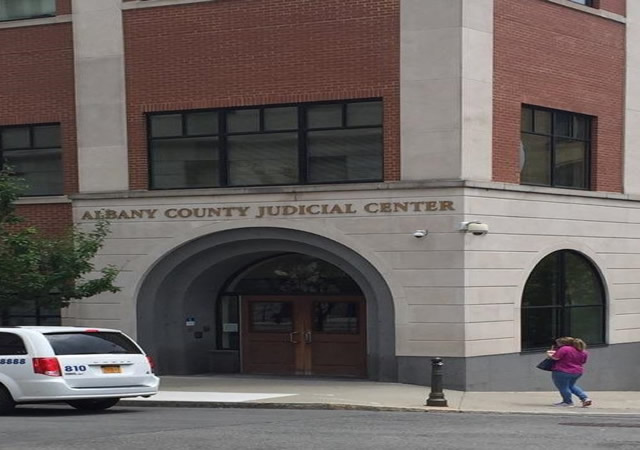 Albany County Judicial Center's main entrance. The entrance contains two doors at street level and a push button to the left of the entry.