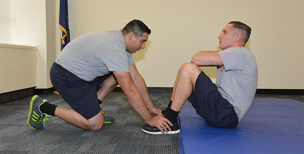 man holding other man's feet down as  he does sit ups