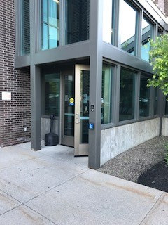 An open door to the courthouse. The entrance is accessed from the sidewalk and there is a push button to open the door to the right of the door located on a column of the building.