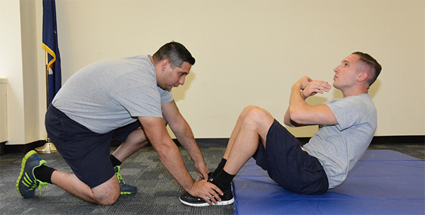 man holding other man's feet as he does sit up without contacting thighs