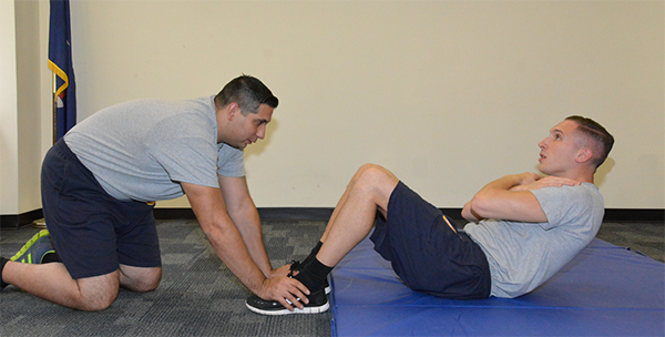 man holding other man's feet down as he does sit ups without touching mat with mid back