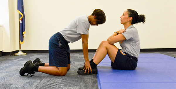 woman holding other woman's feet down as she does sit ups